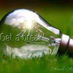 草原に落ちている透明の電球の内部に火花が散っているグラフィック画像