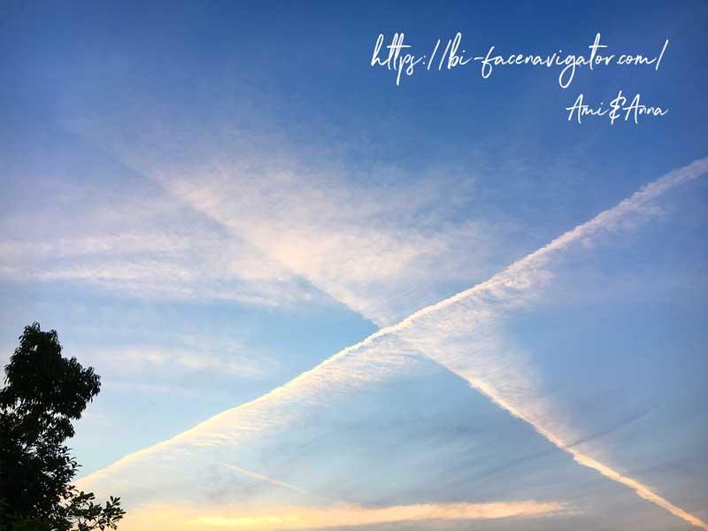 飛行機雲がクロスしてバツ印になっている空の写真