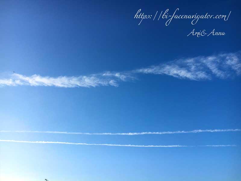 1つの筋雲と2つの飛行機雲が平行に空に出ていて3本の線となっている写真