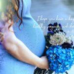 妊娠したお腹を支えるように紫陽花の花束を持っている女性